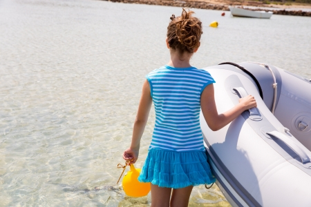 Kid girl in inflatable boat at formentera Estany des Peix near Ibiza photo