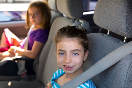 chairs: Kid children girls with safety belt in car vehicle indoor Stock Photo