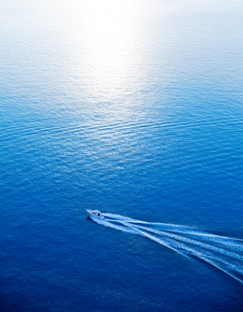 Boat cruising blue Mediterranean sea aerial view in Spain