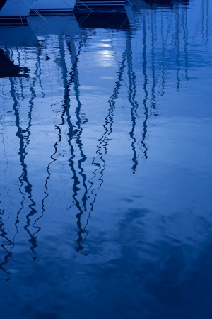 nightfall: Blue water reflection of sailboats boats poles in waves tranquil water Stock Photo
