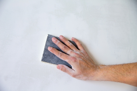 plastering: plastering man hand sanding the plaster in white wall Stock Photo
