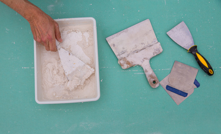 manos sucias: Platering herramientas para el yeso como espátula llana plaste en drywall pladur verde