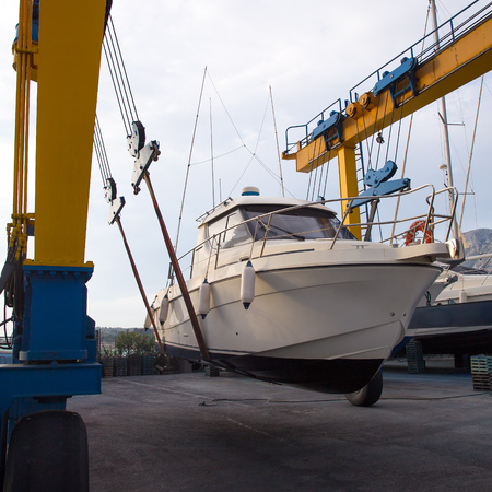 mooring: Boat wheel crane elevating motorboat to yearly paint task