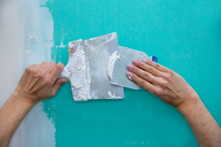 plasterboard: Plastering man hands with plaste on drywall plasterboard hydrophobic construction Stock Photo
