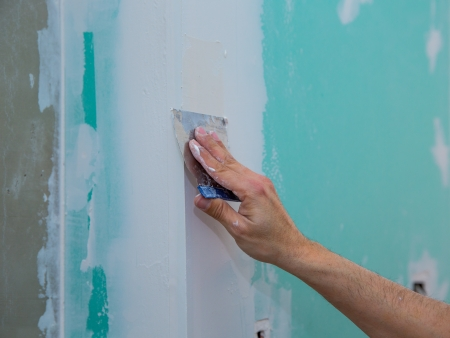 hydrophobic: drywall hydrophobic plasterboard in green plastering seam with trowel Stock Photo