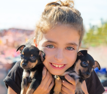blue eyes: kid girl playing with puppy dogs smiling with blue eyes 스톡 사진