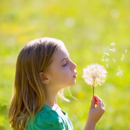 Blond kid girl blowing dandelion flower in green meadow outdoor profile view photo