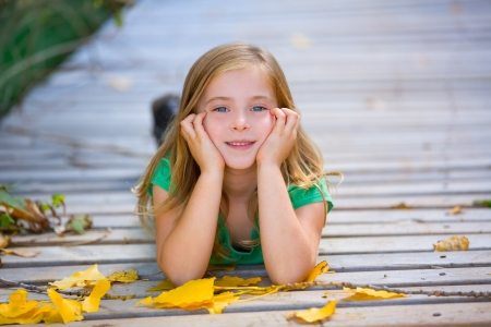 wood deck: Kid girl in autumn wood deck with yellow leaves relaxed outdoor Stock Photo
