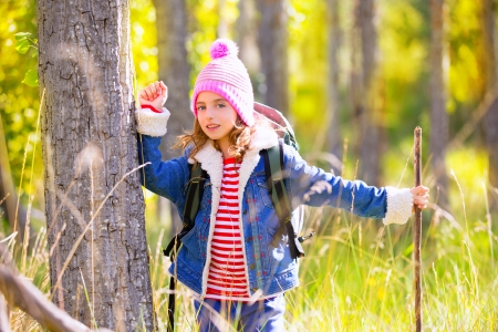 Hiking kid girl with backpack in autum poplar trees forest and walking stick photo