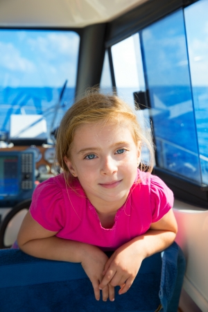 Blond kid girl at boat indoor sailing smiling happy looking camera photo