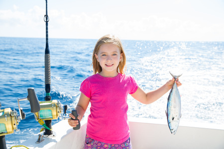 Blond kid girl fishing tuna little tunny happy with trolling catch on boat deck photo