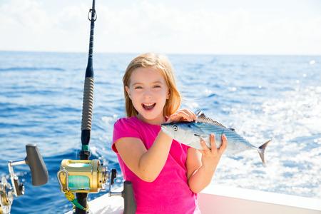 trolling: Chica rubia kid pesca del at�n bonito sarda peces felices con la captura de arrastre en cubierta de barco