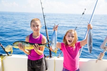 small boat: Happy tuna fisherwomen kid girls on boat with fishes trolling catch with dorado Mahi
