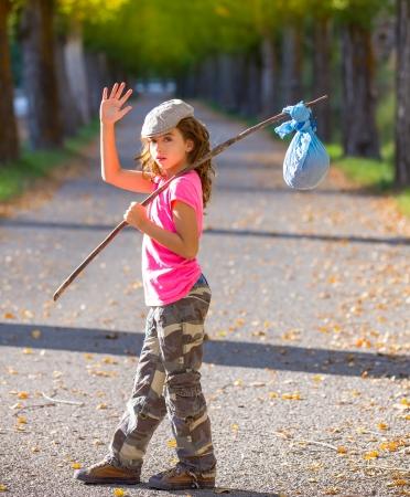 hobo: little kid with hobo stick bag and bundle girl saying goodbye with hand