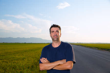 Mid age man in road at meadows posing with crossed arms cereal fields photo