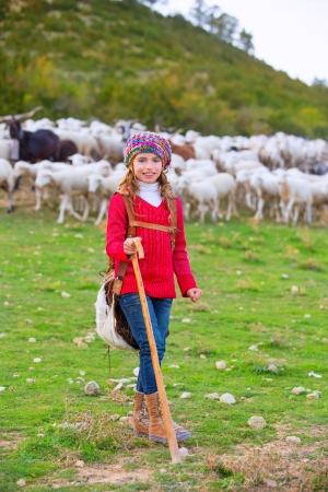 Kid girl shepherdess happy with flock of sheep and wooden stick in Spain photo