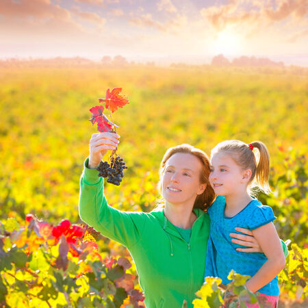 Mother and daughter family on autumn vineyard happy smiling holding grape bunch photo