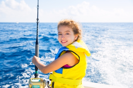 blond  kid girl fishing trolling at boat with rod reel and yellow life jacket Stok Fotoğraf