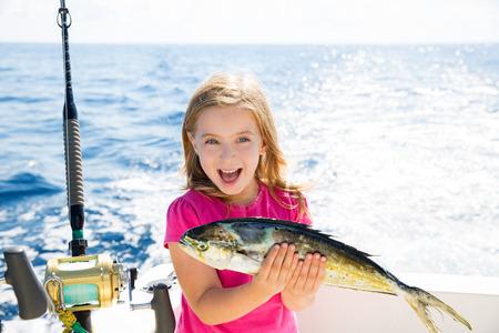 trolling: Chica rubia ni�o a pescar peces Dorado Mahi-mahi feliz con capturas de arrastre en cubierta de barco