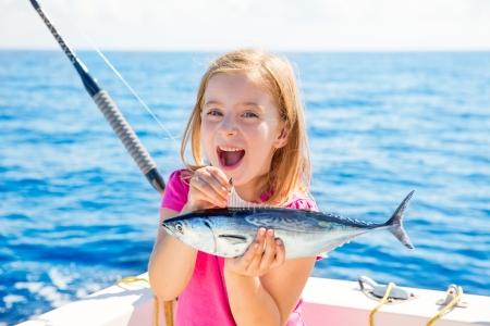 金髪の子供女の子釣りマグロ トローリング満足少しタニー法律事務所は、ボートのデッキ上キャッチ 写真素材 - 24588676