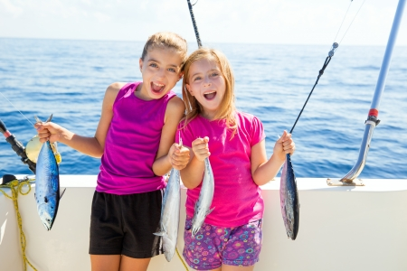 Atún Niñas felices pescadoras cabrito en el barco con los peces de arrastre captura Foto de archivo - 24588678