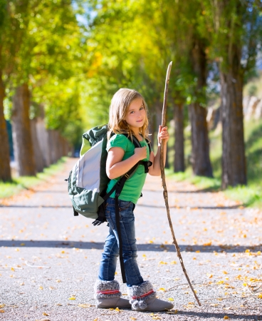 Blond explorer kid girl walking with backpack hiking in autumn trees track holding stick photo