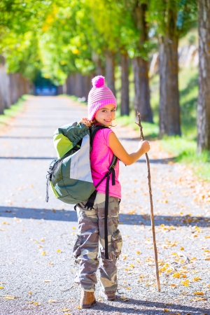 hiking kid girl with walking stick and backpack exploring autumn track and camouflage pants photo