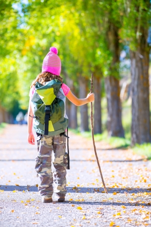 hiking kid girl with walking stick and backpack rear view at autumn track and camouflage pants photo