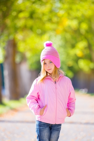 autumn winter kid girl blond with jeans and pink snow cap in trees track photo