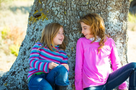 Sister kid girls smiling sit relaxed in a oak tree trunk with jeans photo
