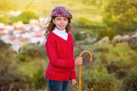 Kid girl shepherdess smiling with wooden baston in Spain village photo