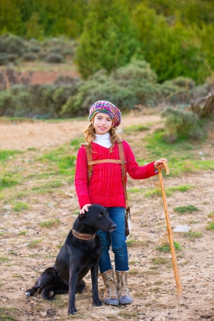 Kid girl shepherdess happy with dog flock of sheep and wooden stick in Spain photo