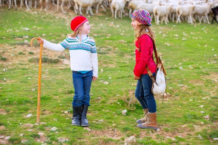 Kid girl shepherdess sisters happy with flock of sheep and wooden stick in Spain photo