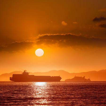 Alcatraz island penitentiary at sunset and merchant ship in san Francisco California USA Stock Photo - 25135245