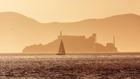 ancient prison: Alcatraz island penitentiary at sunset backlight sailboat in san Francisco California USA