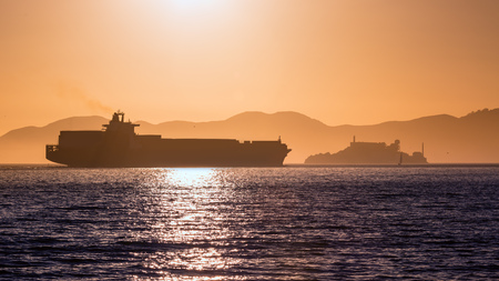 Alcatraz island penitentiary at sunset and merchant ship in san Francisco California USA Stock Photo - 25137502