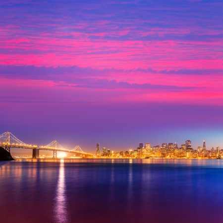 nightfall: San Francisco sunset skyline and Bay Bridge in California with reflection in bay water USA