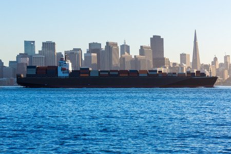 San Francisco Skyline with merchant ship cruising bay at California USA photo