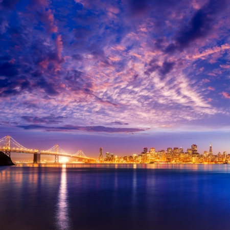 water  scenic: San Francisco sunset skyline and Bay Bridge in California with reflection in bay water USA