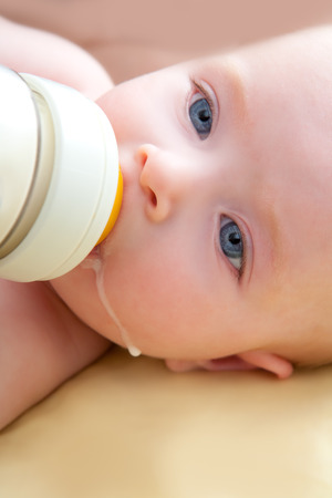 Bond little baby with blue eyes drinking bottle milk photo