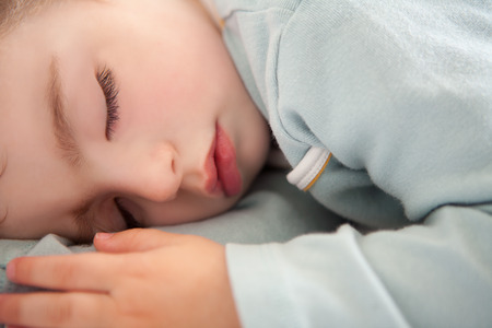 baby toddler sleeping closed eyes relaxed in soft blue photo