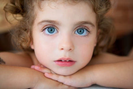 big blue eyes toddler girl looking at camera relaxed Stock Photo