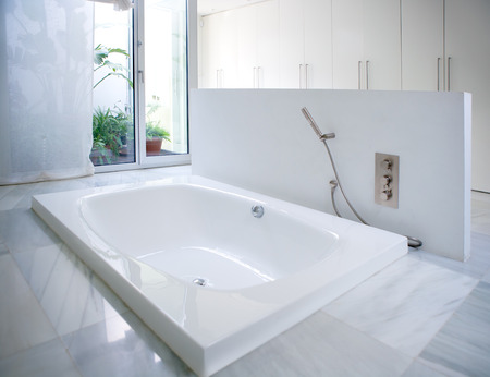 Modern white house bathroom bathtub with marble floor and courtyard skylight photo