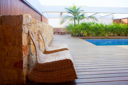 Teak wood modern house outdoor with swing chairs and palm trees pool photo