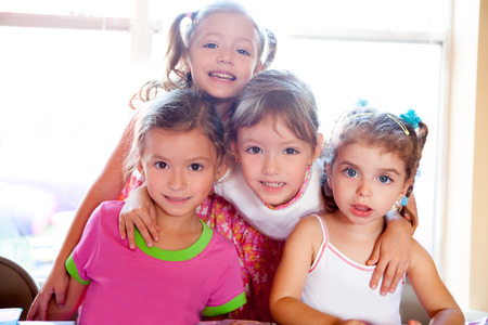 sister and friends kid girls in hug happy together posing looking camera photo