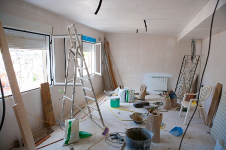 indoors: House indoor improvements in a messy room construction with plaste tools and ladder Stock Photo