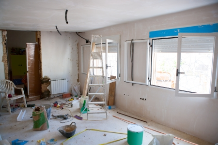 reform: House indoor improvements in a messy room construction with plaste tools and ladder Stock Photo