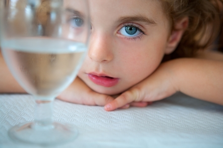 big blue eyes toddler girl looking at camera from a water cup glass on table Stock Photo - 25570319