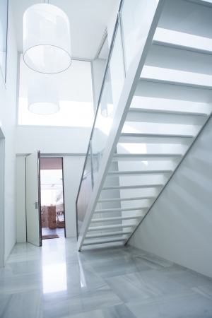 Modern white house entrance hall lobby with stairway and light coming in photo