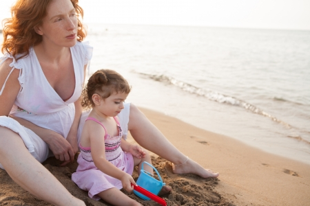 pregnant mother and daughter playing in beach sand of Mediterranean photo